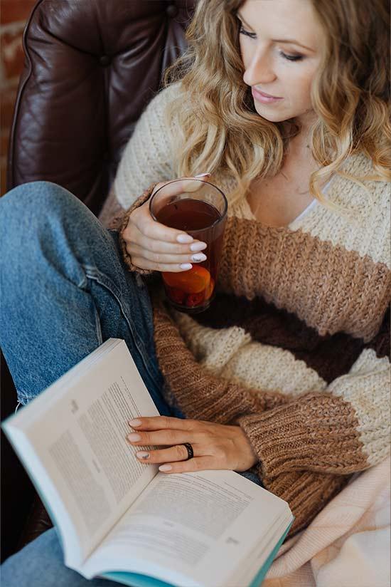 enjoying a cup of iced tea on a leather sofa